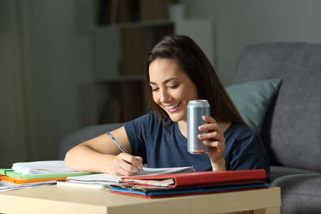 Happy woman studying late hours holding energy drink at home in the night Banco de Imagens