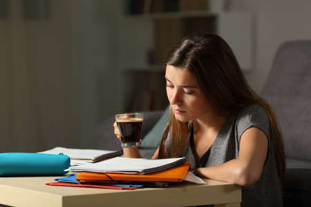 Studious student studying holding a coffee cup in the night at home Banco de Imagens