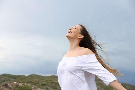 Positieve vrouw die frisse lucht inademt, genietend van de wind