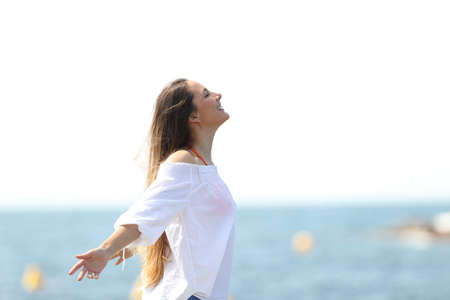 Side view portrait of a relaxed woman breathing fresh air on the beach Archivio Fotografico
