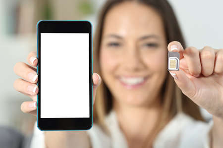 Close up of a happy woman hand showing a sim card and a smart phone