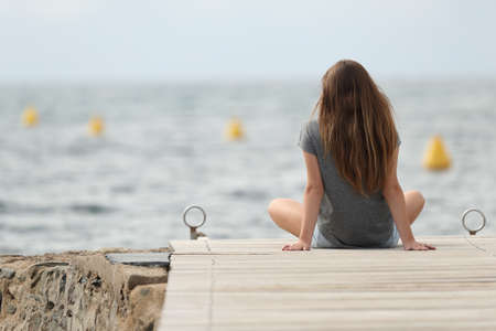 Back view of a teen relaxing looking at the ocean alone on summer
