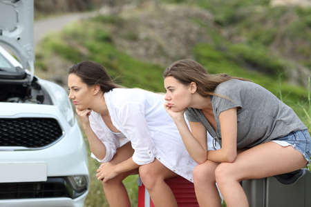 Two frustrated car drivers waiting for assistance after breakdown on summer holidays