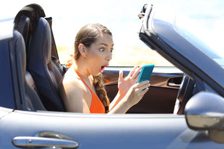 Side view portrait of an amazed car driver watching media content in a smart phone Stock Photo