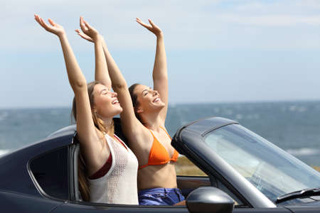 Excited tourists raising arms in a convertible car during a road trip on the beach