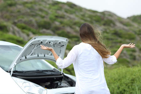 Frustrated driver looking at broken down engine of a car Stock Photo - 103753924