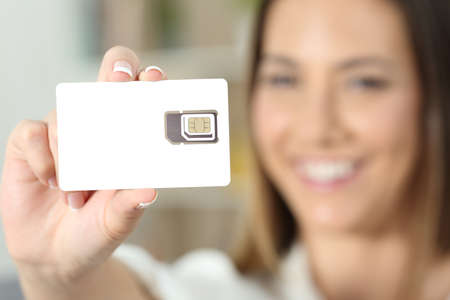 Close up of a happy woman hand holding a new telephony sim card at home