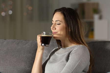 Woman enjoying a cup of coffee in the night sitting on a couch in the living room at home Imagens