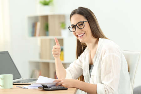 Happy lady doing accounting and gesturing thumbs up at home Reklamní fotografie