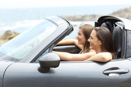 Side view portrait of two tourists driving a car on vacations on the beach Reklamní fotografie