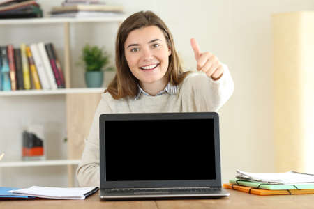 Front view portrait of a happy student showing a mockup laptop screen with thumbs up Reklamní fotografie