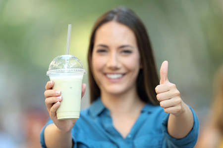 Front view portrait of a satisfied woman holding a smoothie with thumbs up