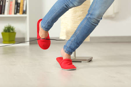 Close up of a woman legs stumbling with an electrical cord at home
