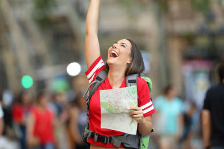 Joyful teen tourist holding a paper map and raising arms on the street Reklamní fotografie