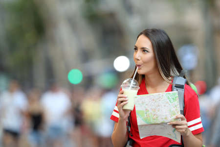 Teen tourist sightseeing drinking smoothie and holding a guide on the street