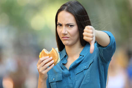 Front view portrait of an angry woman refusing a burger with thumbs down on the street