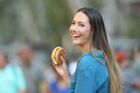 Happy woman holding a burger looking at you on the street Reklamní fotografie
