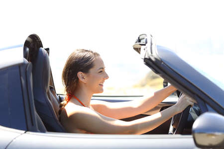 Side view portrait of a single woman driving a convertible car on summer vacation