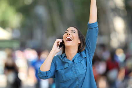 Excited woman receiving good news on the phone raising arms on the street