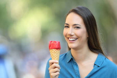 Portrait of a happy woman holding an ice cream looking at you on the street Reklamní fotografie
