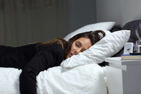 Tired businesswoman lying on a bed sleeping in the night at home or hotel room