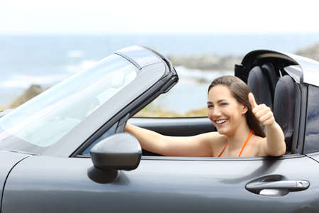 Convertible car driver with thumbs up driving on summer vacation