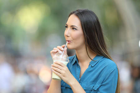 Happy woman drinking a smoothie looking at side on the street