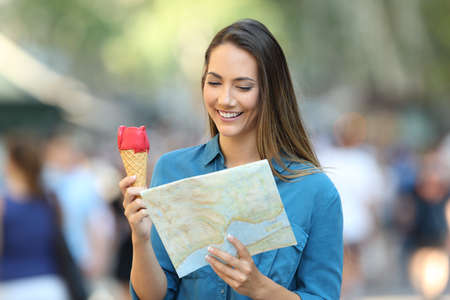Happy tourist holding an ice cream and consulting a map on the street