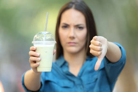 Front view portrait of an angry woman holding a smoothie with thumbs down on the street