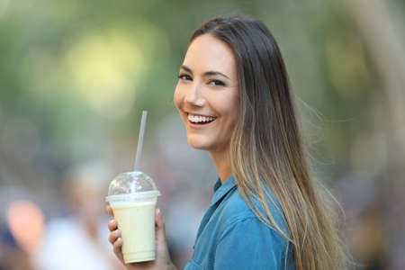 Happy lady holding a smoothie looking at camera on the street Reklamní fotografie