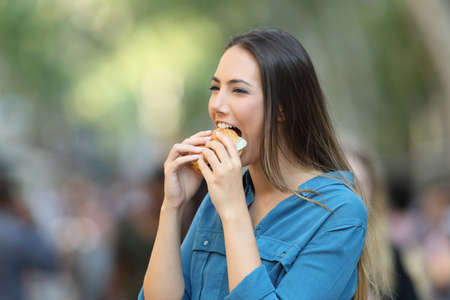 Portrait of a happy woman eating a burger walking on the street Reklamní fotografie
