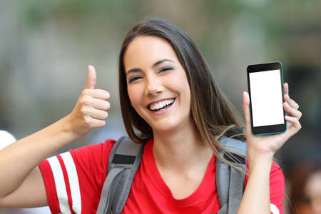 Happy teen showing a blank smart phone screen with thumbs up