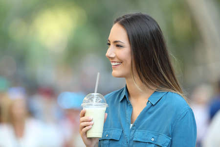 Happy woman holding a smoothie and looking at side on the street