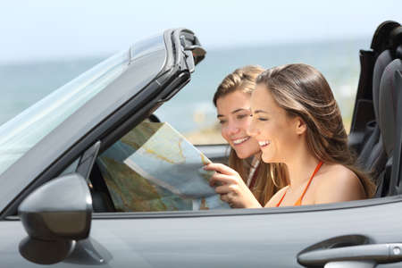 Two tourists reading a map searching destination in a convertible car on summer vacation