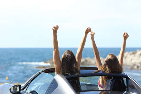 Back view of two joyful tourists watching the sea in a convertible car on summer vacation