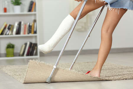 Close up of a disabled girl legs stumbling with a carpet at home