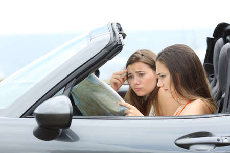 Lost tourists searching destination in a convertible car on summer vacation