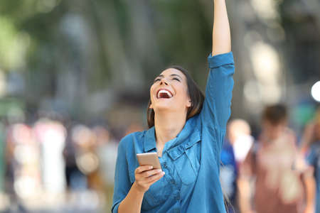 Excited woman holding a smart phone and raising arm on the street