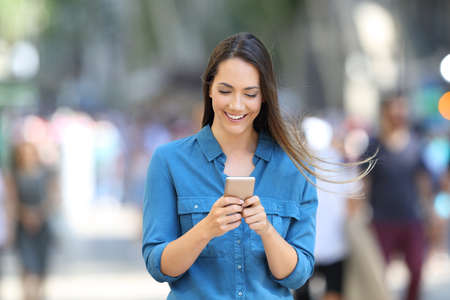 Front view of a happy woman writing message in a smart phone on the street