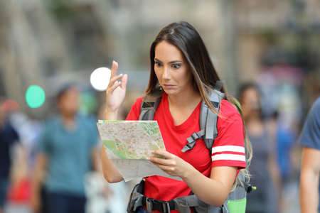 Confused teen tourist searching location in a paper guide walking on the street Reklamní fotografie