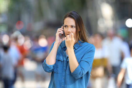 Nervous woman biting nails while is talking on phone on the street