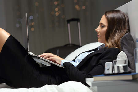 Businesswoman working late hours during business travel lying on the bed of an hotel room