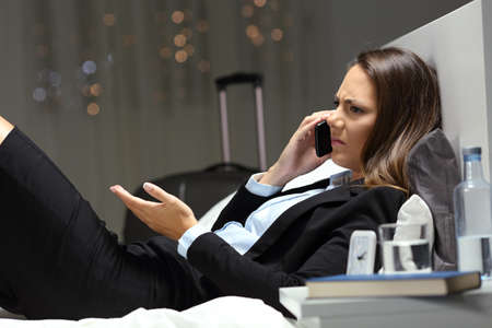 Side view portrait of angry businesswoman claiming on phone on the bed in an hotel room Reklamní fotografie
