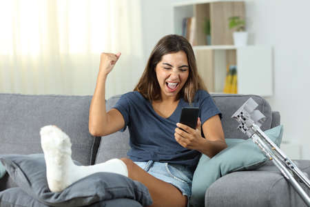 Excited disabled woman receiving online news sitting on a couch in the living room at home