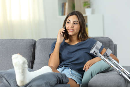 Disabled woman talking on the phone sitting on a couch in the living room at home Stock Photo