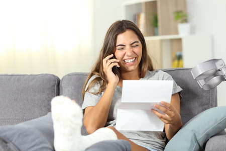 Excited disabled girl confirming letter good news sitting on a couch in the living room at home