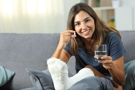 Disabled woman showing a painkiller pill sitting on a couch in the living room at home Stok Fotoğraf