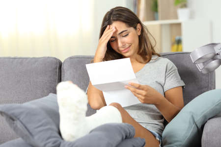 Sad disabled woman reading bad news in a letter sitting on a couch in the living room at home