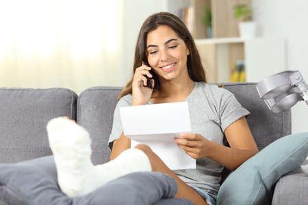 Behinderte Frau am Telefon liest einen Brief, der auf einer Couch im Wohnzimmer zu Hause sitzt
