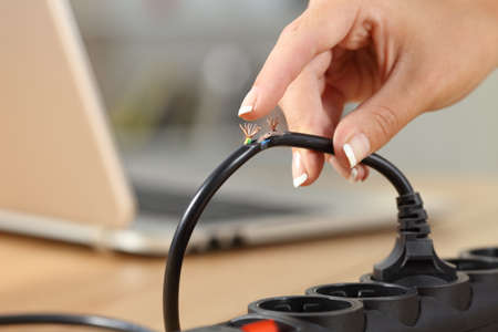 Primo piano di una mano di donna che tiene un pericoloso cavo elettrico danneggiato Archivio Fotografico